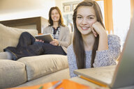Mother and daughter using technology in living room - HEROF06500