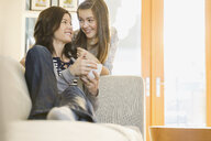 Mother and daughter talking in living room - HEROF06503