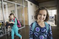 Portrait of confident school girl in corridor - HEROF06530