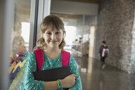 Portrait of confident school girl in corridor - HEROF06533