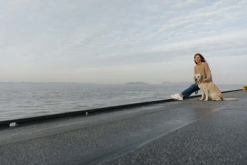 Germany, Hamburg, woman with dog on pier at the Elbe shore - JOSF02880