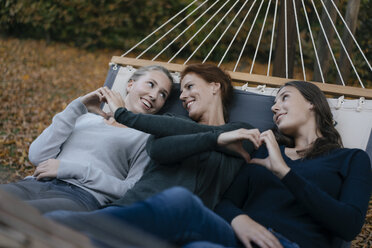 Happy mother with two teenage girls lying in hammock in garden in autumn - JOSF02895