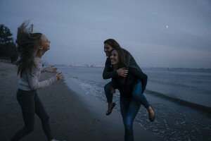 Germany, Hamburg, carefree mother with two teenage girls on the beach at Elbe shore at night - JOSF02901