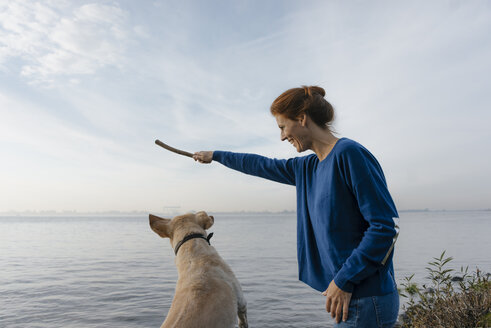 Germany, Hamburg, happy woman playing with dog on beach at the Elbe shore - JOSF02907