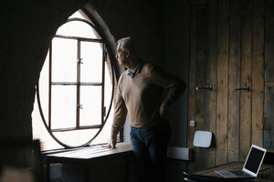 Serious senior businessman looking out of window in office - JOSF02913