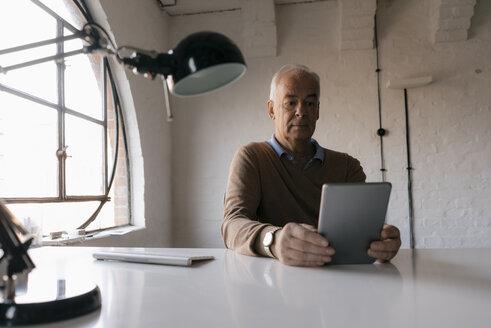 Senior businessman using tablet at desk in office - JOSF02925