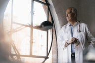 Senior doctor looking out of window in medical practice - JOSF02931