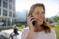 Smiling businesswoman on cell phone outdoors in the city - JOSF02937