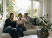 Happy mother with two teenage girls using tablet on couch at home - JOSF02946