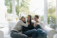 Happy mother with two teenage girls on couch at home - JOSF02952