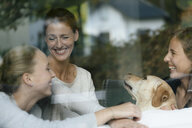 Happy mother with two teenage girls and dog behind windowpane - JOSF02955