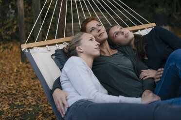 Mother with two teenage girls lying in hammock in garden in autumn - JOSF02961