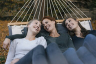 Happy mother with two teenage girls lying in hammock in garden in autumn - JOSF02964