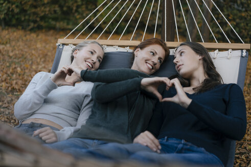 Happy mother with two teenage girls lying in hammock in garden in autumn - JOSF02967