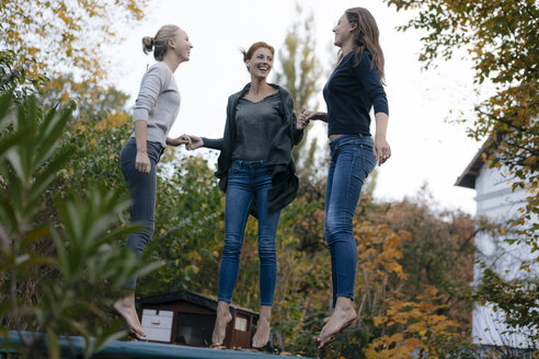 Happy mother with two teenage girls jumping on trampoline in garden in autumn - JOSF02970