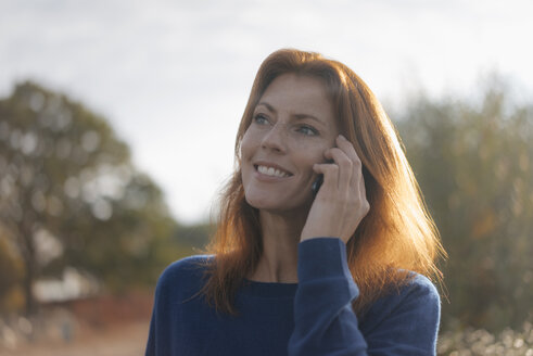 Portrait of smiling woman on cell phone - JOSF02988