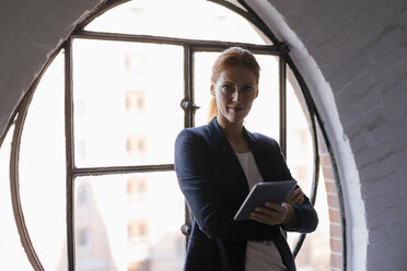 Portrait of confident businesswoman with tablet at the window - JOSF02997