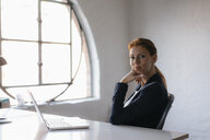 Portrait of businesswoman with laptop sitting at desk in office - JOSF03000