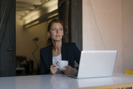 Thoughtful businesswoman sitting at desk in office with cup of coffee and laptop - JOSF03006