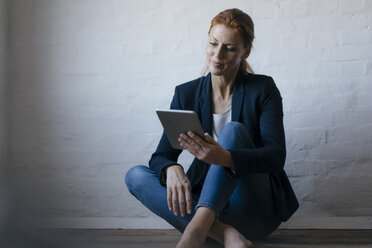 Barefeet businesswoman sitting on floor in office using tablet - JOSF03012