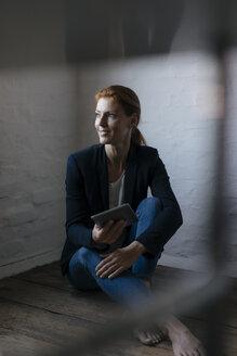 Barefeet businesswoman sitting on floor in office using tablet - JOSF03015