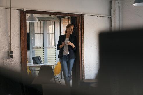 Smiling businesswoman having a coffee break in office - JOSF03018
