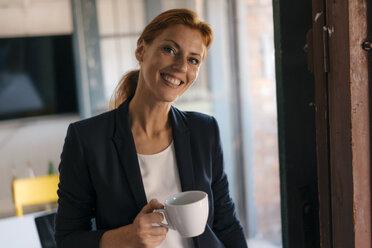 Portrait of smiling businesswoman having a coffee break in office - JOSF03021