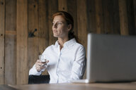Businesswoman sitting at desk with glass of water and laptop - JOSF03030