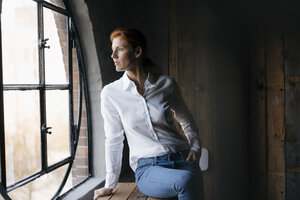 Serious businesswoman looking out of window - JOSF03033