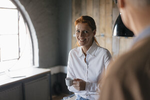 Smiling businesswoman with cup of coffee in office looking at senior man - JOSF03039
