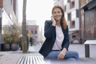 Smiling businesswoman on cell phone sitting outdoors in the city - JOSF03042