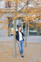 Smiling businesswoman on cell phone outdoors in the city in autumn - JOSF03045