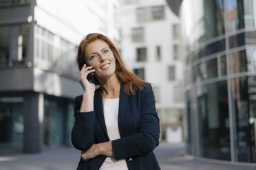 Smiling businesswoman on cell phone outdoors in the city - JOSF03048