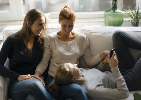 Happy mother with two teenage girls on couch at home with cell phone - JOSF03051