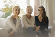 Portrait of smiling mother with two teenage girls sitting on couch at home - JOSF03054