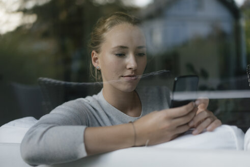 Portrait of serious teenage girl using cell phone on couch at home - JOSF03057