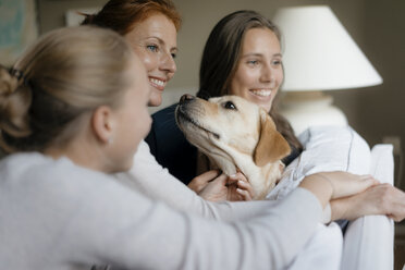 Happy mother with two teenage girls and dog on couch at home - JOSF03063