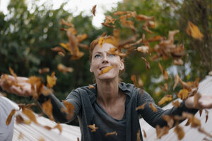 Carefree woman in hammock throwing autumn leaves - JOSF03066