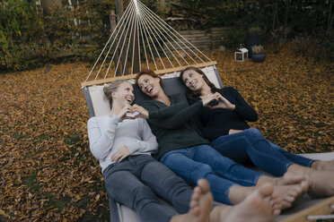 Happy mother with two teenage girls lying in hammock in garden in autumn - JOSF03069