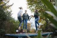 Happy mother with two teenage girls jumping on trampoline in garden in autumn - JOSF03072