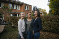 Portrait of happy mother with two teenage girls in garden in autumn - JOSF03075