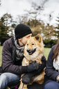 Man embracing Eurasier while sitting with woman at park - ASTF02659