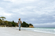 Australia, Tasmania, Maria Island, man strolling on the beach - KIJF02174