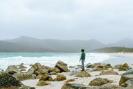 Australia, Tasmania, Man on foggy day in wineglass bay, freycinet national park. - KIJF02198