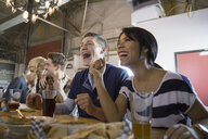 Friends watching TV and cheering at brewery - HEROF06626