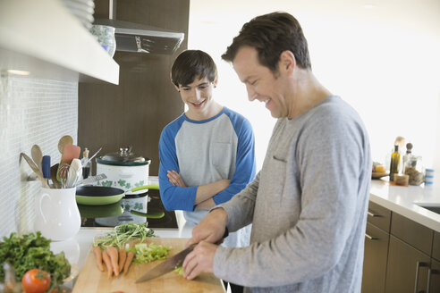 Father teaching son to cook in kitchen - HEROF06671