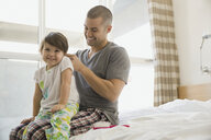 Father fixing daughterŒÍí©s hair on bed - HEROF06728