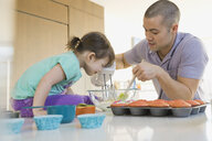 Father and daughter baking cupcakes in kitchen - HEROF06734