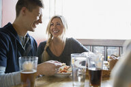 Couple laughing and eating appetizer at brewery - HEROF06827