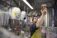 Brewery worker examining beer in beaker - HEROF06890